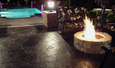 Decorative concrete patio with adjacent built in pool and built in fire pit.