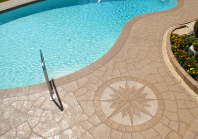 Custom pool deck with compass detail stamped into the concrete.