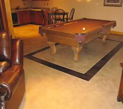 Textured concrete floor in the basement of a home with a pool table over a square detail.