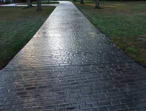 Long brick stamped concrete driveway, stained dark gray and polished.
