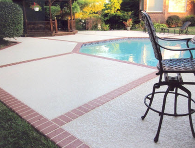 Concrete pool deck, textured with a brick patterned border.