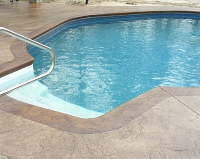 Indoor pool with stamped concrete deck, that's textured and stained.
