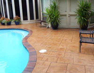 Backyard pool deck that is stamped in a ceramic tile style.